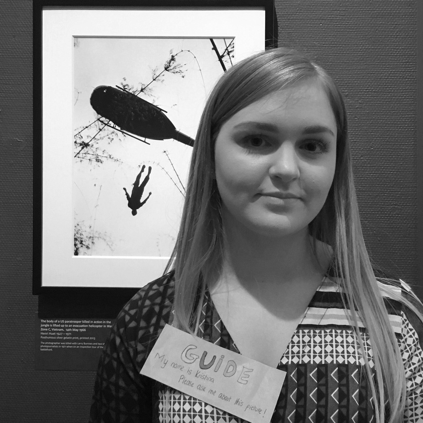 Kristina Rasic next to Henri Huet's image of the body of a US paratrooper killed in action.